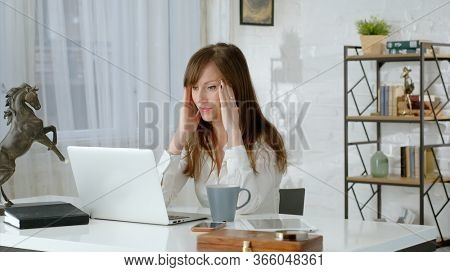 Young business woman working at desk with laptop computer in home office, thinking, having problem and headache . Zoom out.  .