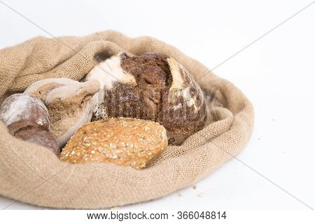 Crusty Rye And Wheat Buns In Rustic Burlap Sack. Closeup Shot. Isolated Object On White Background.