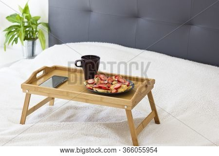 Breakfast Tray Set Up On A Bed With Healthy Pancakes With Strawberry, Hot Drink And Green Plant On T