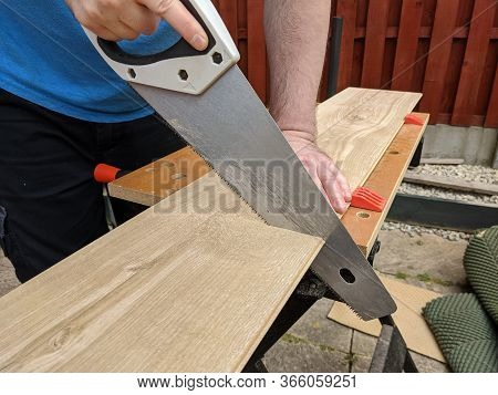 Saw Cutting Laminate Floor Piece For Diy Home Improvement On Workbench