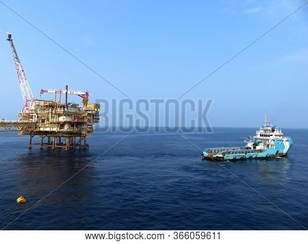 Supply boat (crew boat) transfer worker and cargo by personnel basket from platform to supply boat o