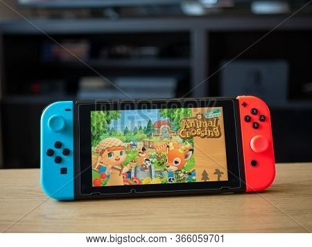 May 2020, Uk: Nintendo Switch Console On Table With Animal Crossing New Horizons Game