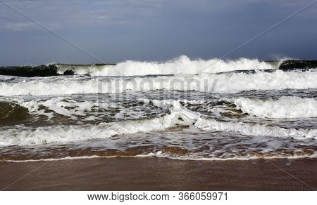 Ocean Waves During A Storm On A Sandy Beach. Sea Water In Spray, Foam And Waves Of Storm Surf.