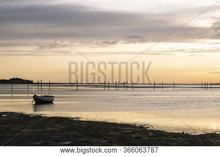 Silhouette Of A Traditional Fisherman Wooden Boat At Sunset In The Bay Of Cadiz, The Sun Reflects On
