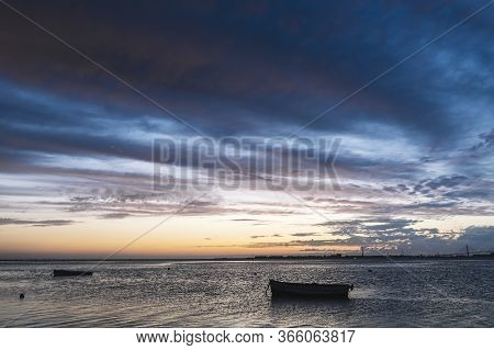 Silhouette Of Traditional Fisherman Wooden Boats Floating In The Calm Water At Sunset In The Bay Of