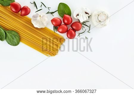 Italian Raw Dry Pasta Spaghetti And Ingredients Isolated On White Background. Copy Space. Top View.