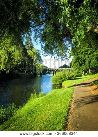 Peaceful Scenery Of A Public Park With River, Sidewalk And Trees. Suitable To Illustrate An Article