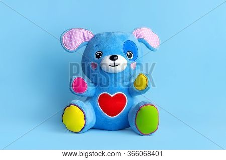 Blue Soft Children's Toy Puppy With Funny Ears, Multi-colored Paws And Red Heart On Blue Background