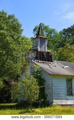 Country Church Has Extensive Damage To Wooden Steeple And Roofline. Steeple Is Shingled With Green.
