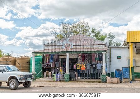 Fouriesburg, South Africa - March 18, 2020: A Street Scene, With A Clothing Store And A Vehicle, In