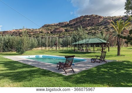 Fouriesburg, South Africa - March 18, 2020: Landscape With A Swimming Pool And Deck Chairs At Uithoe