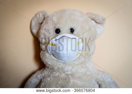 Cute Teddy Bear With Protective Medical Mask On Yellow Background. Concept Of Pediatric Treatment, H