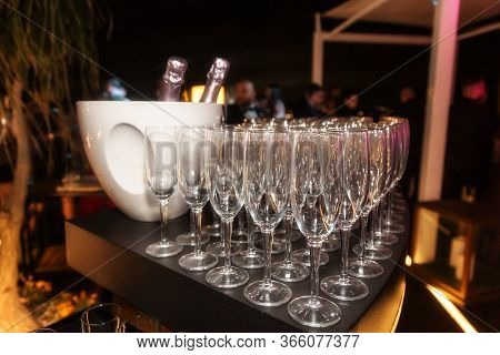 Sparkling Wine Bottle In The Ice Bucket And Wine Glasses In A Restaurant Setting.
