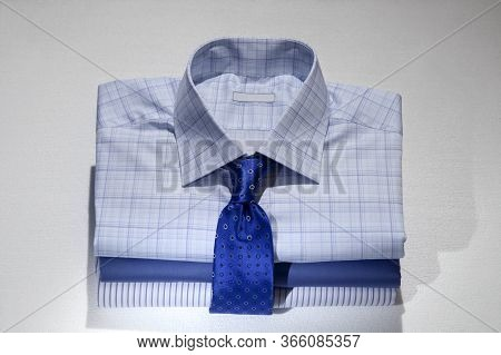 Folded Men's Shirts And Ties, Isolated On White Background.