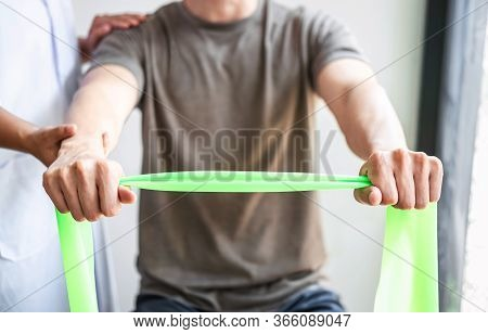 Doctor Or Physiotherapist Working Examining Treating Injured Arm Of Athlete Male Patient, Stretching