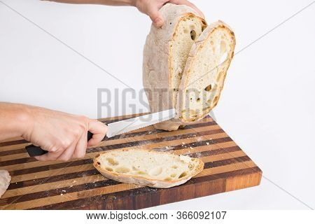 Baker Cutting Round Loaf Of Crusty Wheat Bread In Slices On Chopping Board. Isolated Object On White