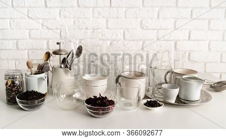 Ceramic And Glass Cups And Tableware On The Table On White Brick Wall Background