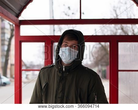 Guy In A Medical Mask Stands At A Bus Stop. Isolated To Avoid Viral Disease Covid-19 Measles Flu Chi