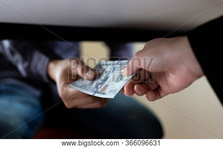 Businessmen give dollars under the table to bribe employees in signing contracts for the purchase of