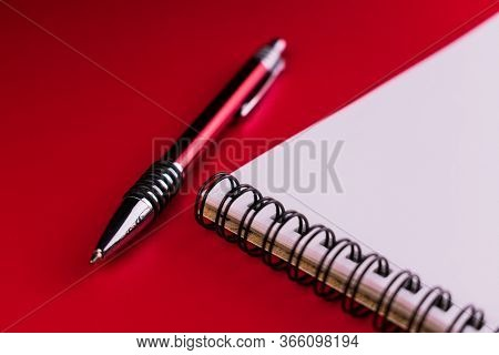 Notebook And Red Pen On A Red Background. Composition Red On Red.