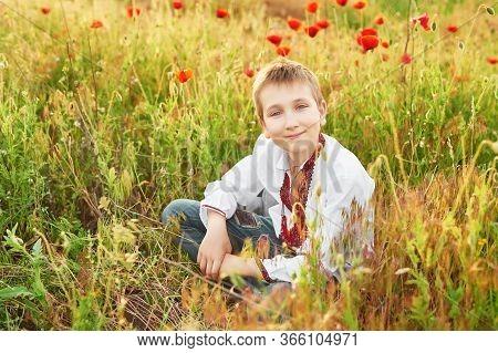 Ukraine's Independence Day. Child Boy In An Embroidered Shirt In Poppy Field. Ukraine In Field. Chil