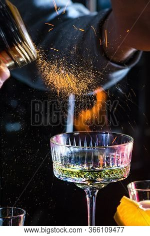 Male Bartender Holds Fired Up Sugar Above Delicious Alcohol Cocktail. Extream Fired Coctail