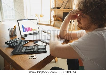 Caucasian Upset And Despair Man Watching Financial And Economical Graphs Going Down During Coronavir