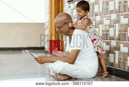 Little Granddaughter Playing With Grandfather By Pulling Grandpas Ears At Home - Concept Of Together