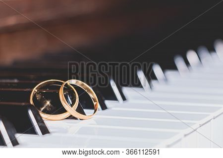 Gold Wedding Rings On A Piano Key