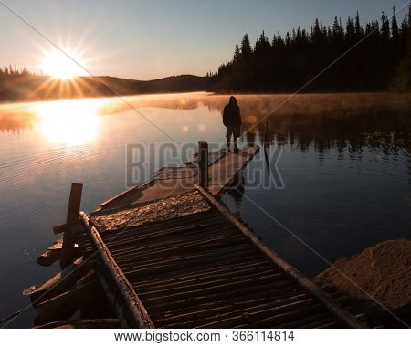Solitary Man Standing On A Dock On A Lake With Sun Setting