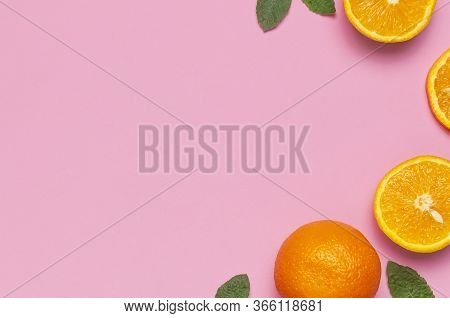 Fruit, Creative Summer Concept. Fresh Juicy Whole And Sliced Orange, Mint Leaves On Pink Background.