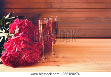 Two Glasses Of Rose Champagne And Red Peony Flowers On Wooden Table. Selective Focus. Toned Image. V