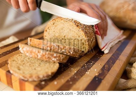 Woman Cooking Breakfast And Cutting Crusty French Loaf In Slices On Chopping Board, Holding Bread Wi