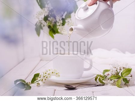 Tea Ceremony. White Teapot And Cup On A White Wooden Table With Flowers And With A Bokeh Of Green Le
