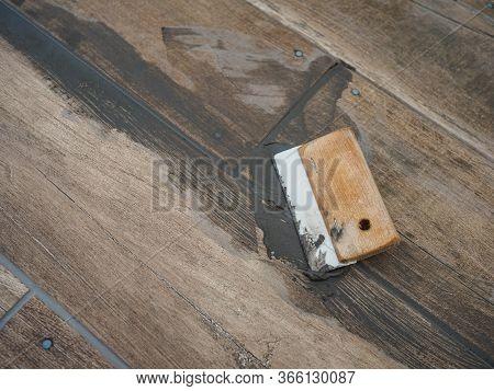 Grouting Between Ceramic Tiles. Work Tool Spatula. Repair In The Room
