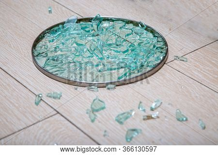 A Close-up Of A Broken Glass Lid Lies On A Stake Of Tile. Shards Of Glass Shine. Soft Focus, Side Vi