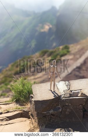 A Wooden Man Stands On A Cliff Of A Mountain At The Precipice And Looks Into The Distance In The Sun
