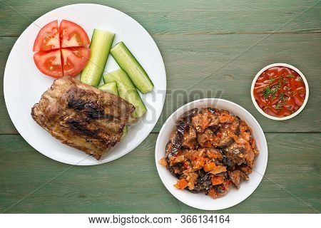 Grilled Pork Ribs With Sliced Cucumbers And Tomatoes On A White Plate. Pork Ribs On Green Wooden Bac