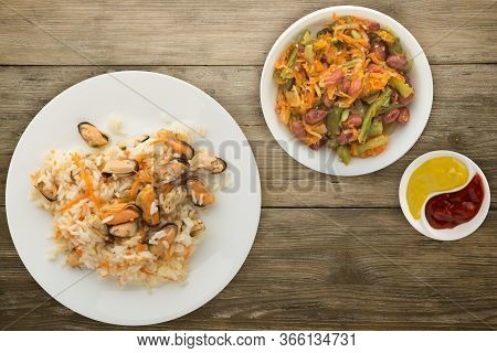 Rice With Mussels And Carrots On A White Plate. Rice With Mussels And Carrots On A Wooden Background