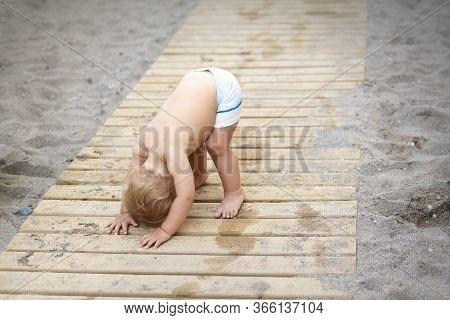 Cute Adorable Funny Little Caucasian Blond Toddler Boy In Swimming Shorts Standing Upside Down On Wo
