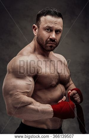 Shirtless Adult Male Bodybuilder Showing His Big Biceps In A Dark Studio On A Grey Background, Looki