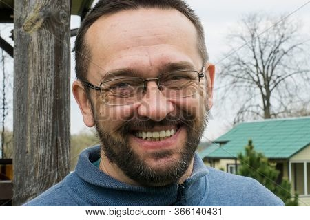 Smiling adult bearded man in the yard of a village house