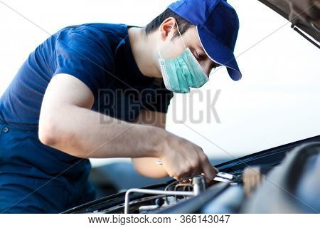 Mechanic fixing a car engine wearing a mask, coronavirus concept