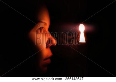 Beautiful Young Woman In The Dark Looks Into The Keyhole Glowing With Red Mysterious Light (high Iso