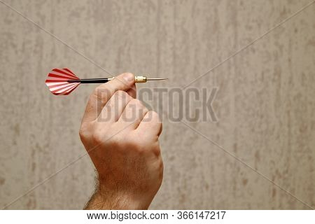 A Man Holds A Dart For Playing Darts, Takes Aim, Ready To Throw Darts.