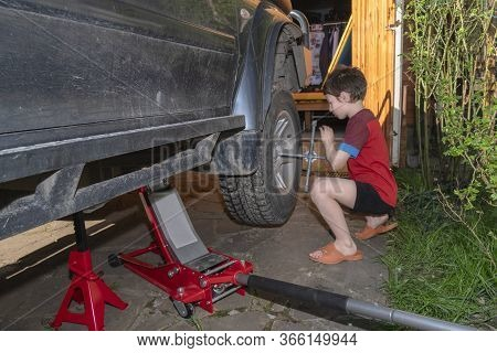 Boy Unscrews The Nuts On The Wheel Of Big Off-road Car. Wheel Replacement In The Yard. Side View.