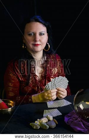 A Young Soothsayer In A Magic Salon With Cards In Her Hands On A Black Background.