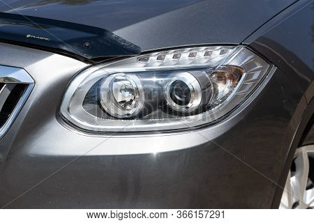 Novosibirsk/ Russia - May 03 2020: Brilliance V5, Glowing Headlight Of A Modern Gray  Car Close-up.
