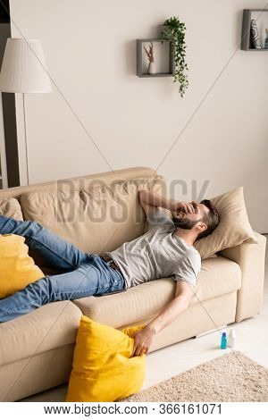 Young bearded man being in depression because of coronavirus isolation lying on sofa and covering face with hand