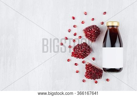 Juicy Red Garnet Juice In Glass Bottle With Blank Label, Grains Of Fruit On White Wood Board, Top Vi